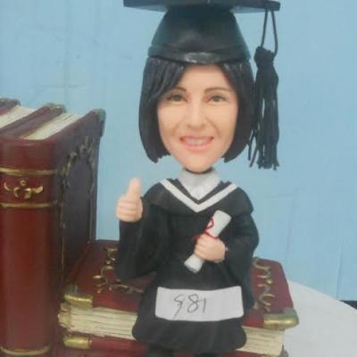statuina personalizzata di laureata su libri per cerimonie di laurea