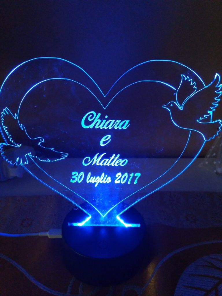 luce a led blu che illumina il regalo di San Valentino, un cuore in plexi inciso